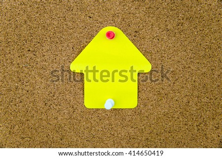 Blank yellow paper note in shape of house pinned on cork board with white and red thumbtacks, copy space available - stock photo