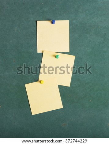 Blank Yellow paper posted on green board with tack pin for text and background - stock photo