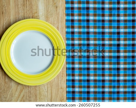 Blank yellow plate on wooden table and checked tablecloth background - stock photo
