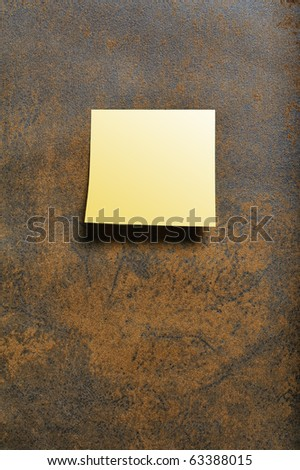 Blank yellow post-it attaches on Brown leather texture - stock photo