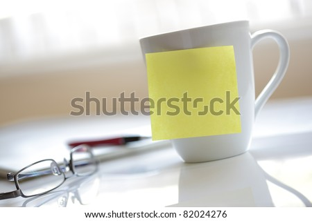 Blank yellow sticky note on a coffee cup ready for message - stock photo