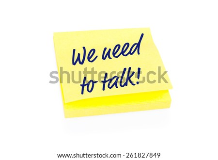 Blank yellow sticky note on block with handwritten message We Need To Talk. Shadow and reflection on white background