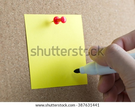 Blank yellow sticky note with hand hold a marker pen