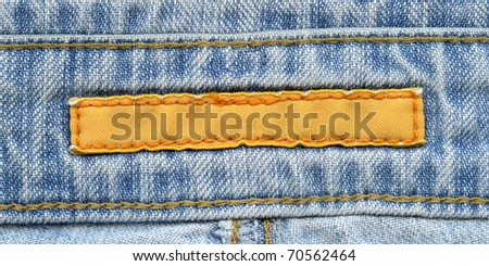 Blank yellow textile label  sewed on a blue jeans. Can be used as background for your text. - stock photo