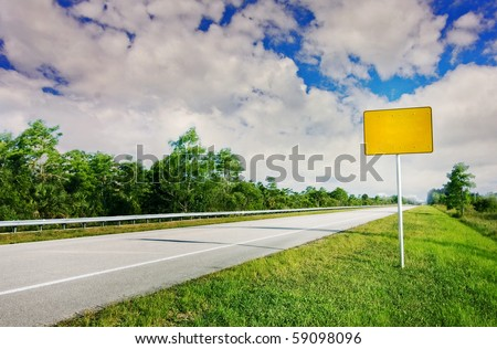 Blank yellow traffic sign by the highway road going through a natural landscape - stock photo