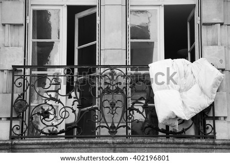 Blanket is dried, hanging out of the window of  typical Parisian house. Paris, France. Aged photo. Black  and white. - stock photo