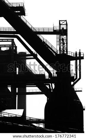 Blast furnace silhouette at heavy steel machinery - stock photo