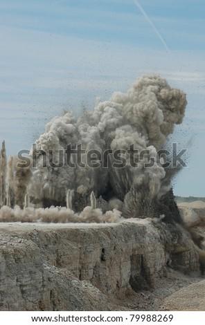 Blast in open cast mining quarry - stock photo