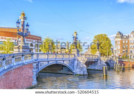 Blauwbrug Blue Bridge over Amstel river in Amsterdam at sunny spring evening, Holland, the Netherlands.