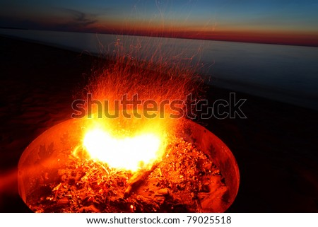 Blazing campfire at sunset along the beautiful beach of Lake Superior in northern Michigan - stock photo
