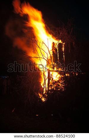 Blazing campfire on a black background - stock photo