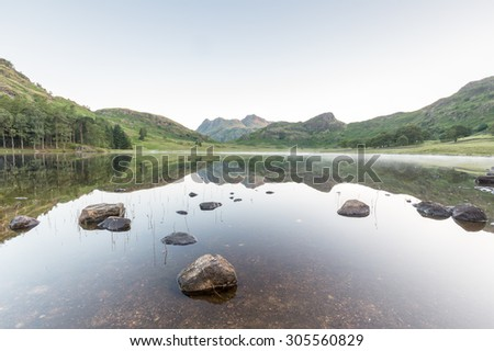 Blea Tarn reflection, the Langdale Pikes in the UK Lake District - stock photo
