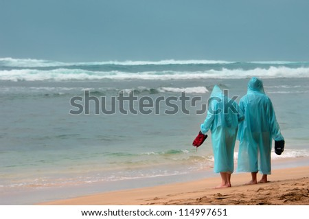 Bleary day in paradise.  Two vacationers stand in wet suits watching the waves on the shore of Kauai, Hawaii. - stock photo