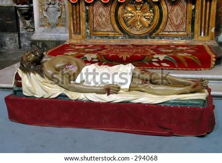 Bleeding jesus lies on a bed in a roman church, - stock photo