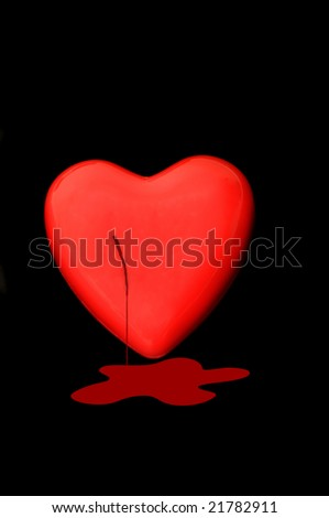 Bleeding Red heart isolated on a dark back ground - stock photo