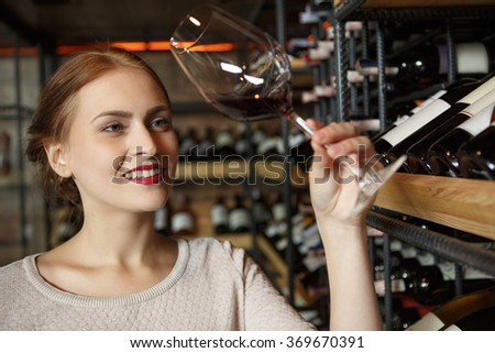 Blend of taste. Closeup portrait of a beautiful young woman posing with a glass of red wine at the wine store cellar - stock photo