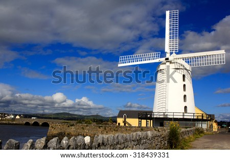 Blennerville Windmill - white windmill with the blue sky with clouds background in Tralee Bay (town of Blennerville, Ireland). This windmill is the tallest of it's kind in Europe.   - stock photo
