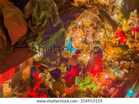 Blessed Virgin Mary and Saint Joseph watch over the Holy Child Jesus in a manger in the straw as the ox and the donkey are warming while the three wise men bring gifts of gold, frankincense and myrrh - stock photo
