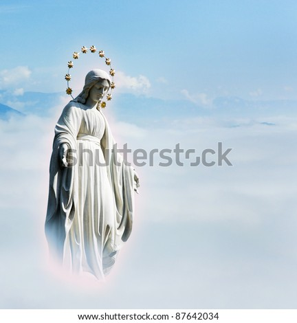 Blessed Virgin Mary at the sky background. Mother Mary statue. Holy phenomenon of Holy Maria in the light of glow in the sky above the clouds. - stock photo