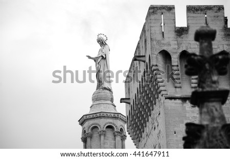 Blessed Virgin Mary. Golden statue of Madonna blessing from the top of Notre Dame Cathedral and the walls of Papal palace in Avignon (France) Black and white photo. - stock photo