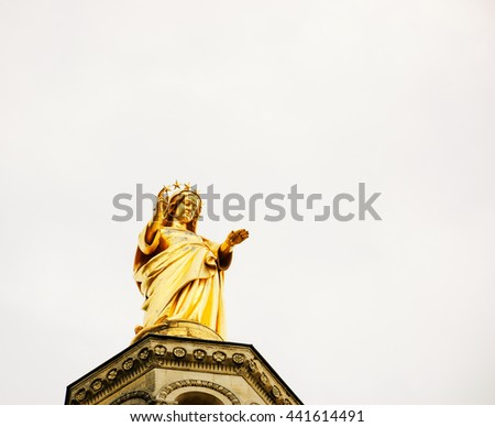 Blessed Virgin Mary. Golden statue of Madonna looking from the top of Notre Dame Cathedral. Avignon (France)  - stock photo