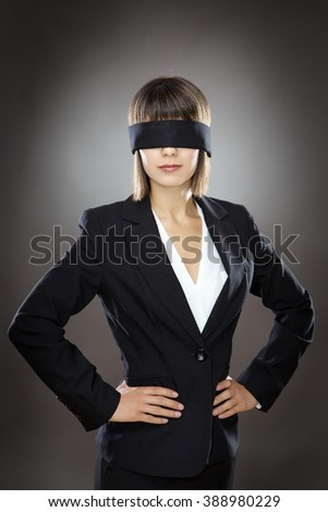 blind folded business woman low key lighting shot in the studio on a gray background