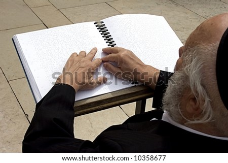 Blind israelite being prayed in the wailing wall according to Braille's book. - stock photo