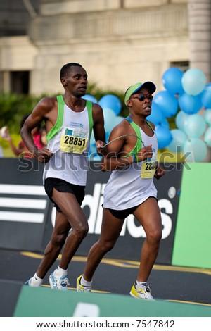 Blind Kenyan runner Henry Wanyoike with his guide Joseph Kibunja Gachui at the end of Singapore Marathon 2007 - stock photo