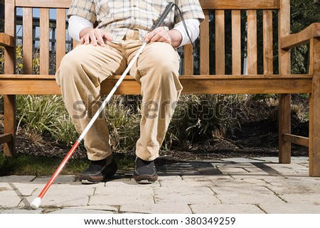 Blind man sitting on a bench - stock photo