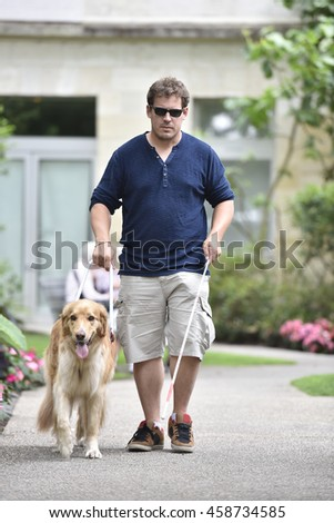 Blind man walking in park with dog assistance - stock photo