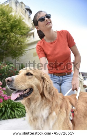 Blind woman petting her guide dog - stock photo