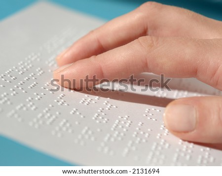 Blind woman reading text in braille - stock photo