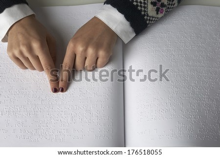 Blind woman reading text in braille language - stock photo