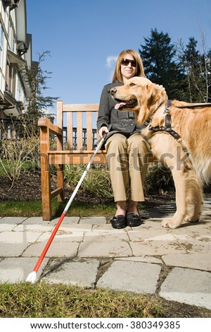 Blind woman with a guide dog - stock photo