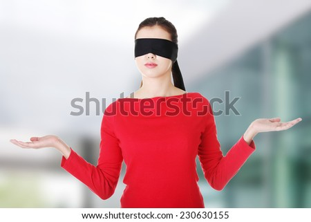 Blindfold woman presenting copy space on her palms - stock photo