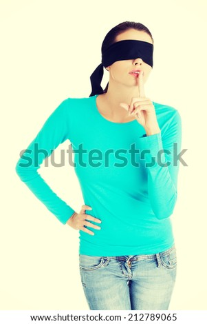 Blindfold woman with finger on lips. Gesturing for quiet and keeping secret - stock photo