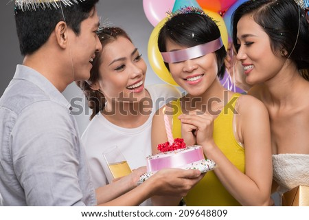 Blindfolded birthday girl receiving a cake from her friends