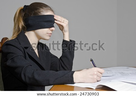 Blindfolded businesswoman signing papers - stock photo