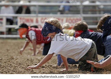 Blindfolded children in a 'Watermelon Crawl' race in rural/country America (shallow focus). - stock photo