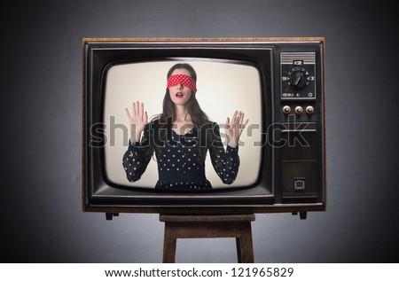 Blindfolded girl on old TV screen. - stock photo