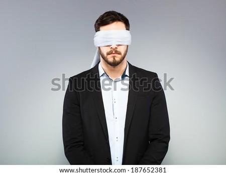 blindfolded office man in black coat - stock photo