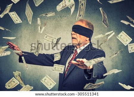 Blindfolded senior businessman trying to catch dollar bills banknotes flying in the air on gray wall background. Financial corporate success or crisis challenge concept   - stock photo
