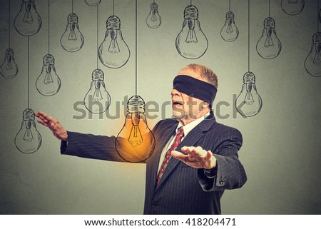 Blindfolded senior man walking through light bulbs searching for bright idea isolated on gray wall background  - stock photo