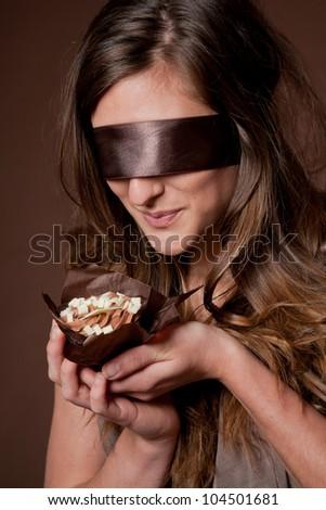 Blindfolded woman holding chocolate cake - stock photo