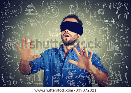 Blindfolded young business man searching walking through complicated social media financial data plan. Sightless entrepreneur analyst managing corporate unknown  financial economy risk concept  - stock photo