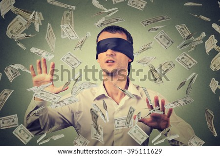 Blindfolded young businessman trying to catch dollar bills banknotes flying in the air isolated on gray wall background. Financial corporate success or crisis challenge concept - stock photo