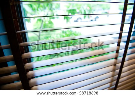 blinds inside a window being opened to show sunlight. - stock photo