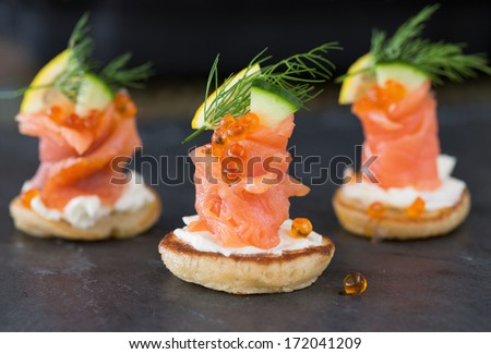 Blini with smoked salmon and sour cream, garnished with dill. Close-up view on dark background