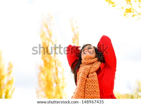 Blissful beautiful woman enjoying autumn season outdoors. Happy caucasian brunette bliss and satisfaction in fall. Autumnal background for copy space. - stock photo