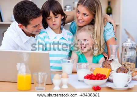 Blissful family using laptop during the breakfast in the kitchen - stock photo